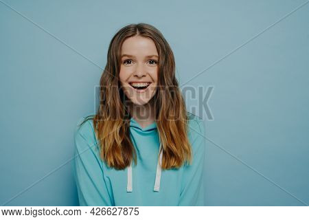 Studio Shot Of Attractive Happy Young Teenage Girl In Casual Clothes Looking At Camera With Happy Fa
