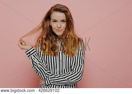 Beautiful Young Caucasian Woman Dressed In Casual Clothes Playing With Hair And Looking At Camera, C