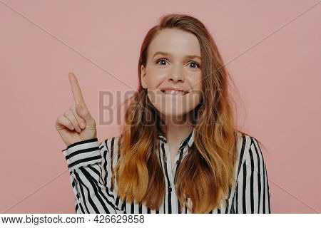 Studio Shot Of Young Emotional Woman In Casual Clothes Biting Lower Lip And Pointing Up At Copy Spac