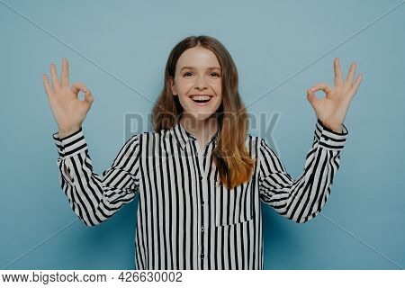Laughing Young Female With Wavy Brown Hair Showing Okay Sign With Both Hands Wearing Striped Black A