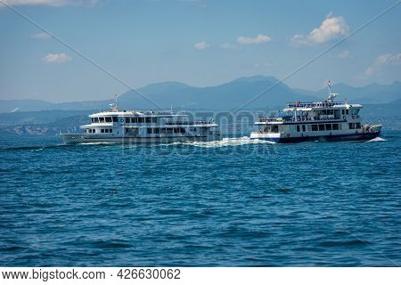 Two Ferry Boats In Motion In Front Of The Small Village Of Bardolino On Lake Garda (lago Di Garda),