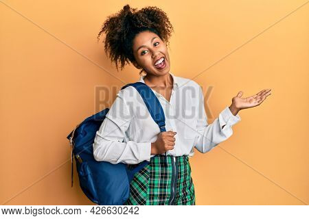 Beautiful african american woman with afro hair wearing student backpack celebrating achievement with happy smile and winner expression with raised hand