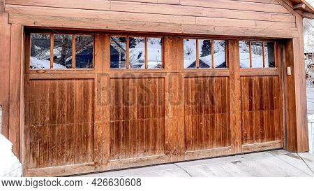 Pano Garage Exterior With Snowy Gable Roof Over Glass Paned Door And Wooden Wall.