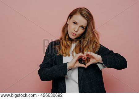 Beautiful Young Female With Wavy Ginger Hair In Formal Dark Jacket And White Top Showing Heart Shape