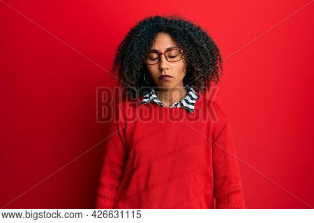 Beautiful african american woman with afro hair wearing sweater and glasses looking sleepy and tired, exhausted for fatigue and hangover, lazy eyes in the morning.