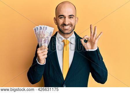 Young hispanic business man holding russian 500 ruble banknotes doing ok sign with fingers, smiling friendly gesturing excellent symbol