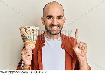 Young hispanic man holding 500 norwegian krone banknotes smiling with an idea or question pointing finger with happy face, number one