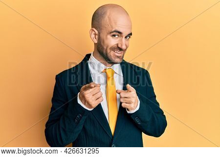 Young hispanic man wearing business suit and tie pointing fingers to camera with happy and funny face. good energy and vibes.