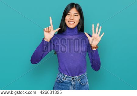 Beautiful young asian woman wearing casual clothes showing and pointing up with fingers number seven while smiling confident and happy.
