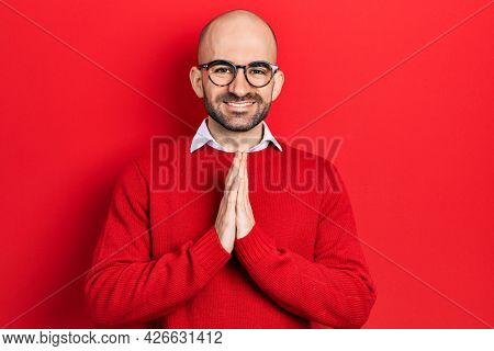 Young bald man wearing casual clothes and glasses praying with hands together asking for forgiveness smiling confident.