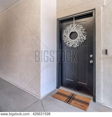 Square Apartment Unit With White Wreath Dark Gray Door And Doormat At The Entrance