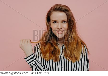 Beautiful Happy Young Female In Stripy Black And White Blouse Holding Strand Of Hair And Smiling At