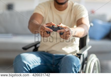 Cropped View Of Handicapped Black Guy In Wheelchair Enjoying Online Videogame, Having Fun At Home, C