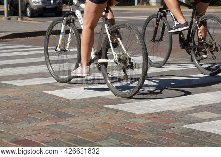 Cyclists Cross The Street At A Pedestrian Crossing