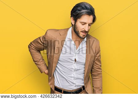 Young hispanic man wearing business clothes suffering of backache, touching back with hand, muscular pain