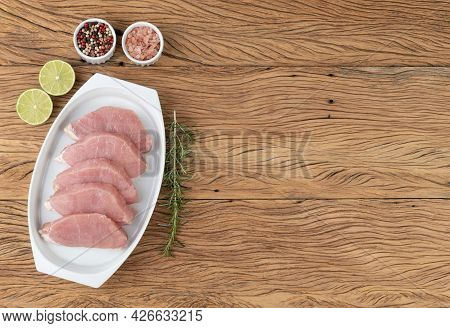Sliced Raw Pork Loin Meat Over White Plate With Seasonings And Copy Space.