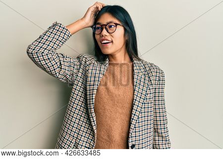 Young chinese woman wearing business style and glasses smiling confident touching hair with hand up gesture, posing attractive and fashionable