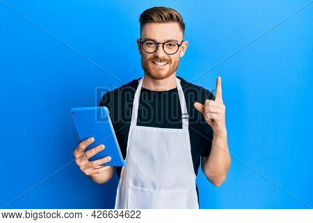 Young redhead man wearing professional apron using touchpad smiling with an idea or question pointing finger with happy face, number one