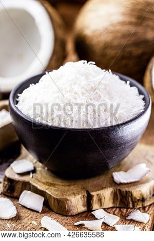 Grated Coconut Inside A Clay Bowl, With Coconut And Coconut Pieces In The Background, Culinary Ingre