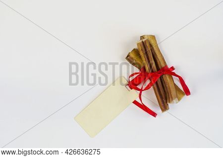 Dog Treats And Rectangular Sales Tag On White. Air Dried Pet Chew Sticks. Bully Sticks. Beef Pizzle.
