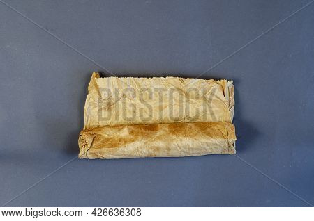 Twisted Dirty Brown Paper Bag On Gray Background. Paper Bag Used For Packing Lunch, Groceries. Recyc