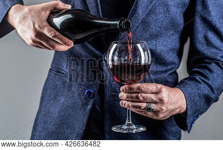Waiter Pouring Red Wine In A Glass. Sommelier Man, Degustation, Winery, Male Winemaker. Red Wine Is