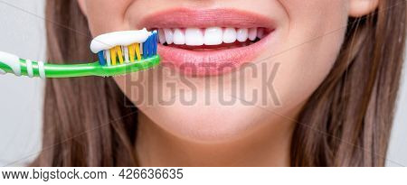 Portrait Of A Smiling Cute Woman Holding Toothbrush. Smiling Woman With Healthy Beautiful Teeth Hold