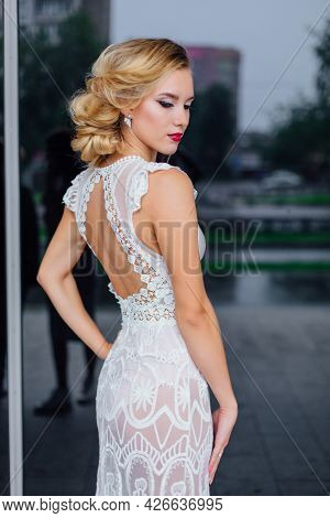 Beautiful Blond Bride In White Wedding Dress Standing Near Mirror Window Outdoors.