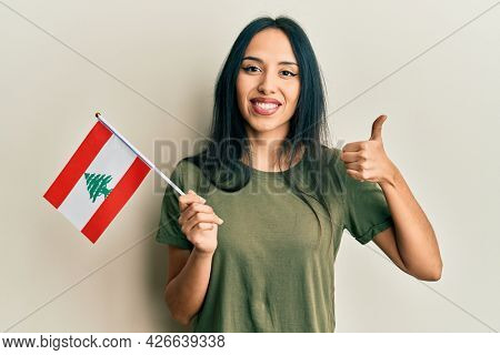 Young hispanic girl holding lebanon flag smiling happy and positive, thumb up doing excellent and approval sign