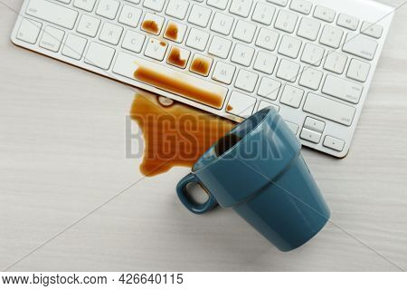 Cup Of Coffee Spilled Over Computer Keyboard On White Wooden Table, Flat Lay