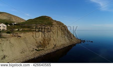 Stunning Aerial View Of The Open Sea And A Small Green Island. Shot. Breathtaking Green Grass Covere