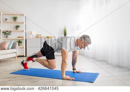 Sporty Mature Man Doing Running Plank Exercise Training On Sports Mat In Living Room At Home, Free S