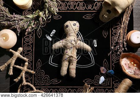 Voodoo Doll Pierced With Pins Surrounded By Ceremonial Items On Table, Flat Lay. Curse Ceremony