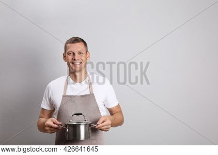 Happy Man With Cooking Pot On Light Grey Background. Space For Text
