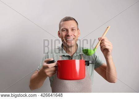 Happy Man With Cooking Pot And Ladle On Light Grey Background