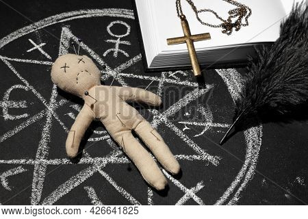 Ceremonial Items And Voodoo Doll In Ritual Circle Drawn On Black Table