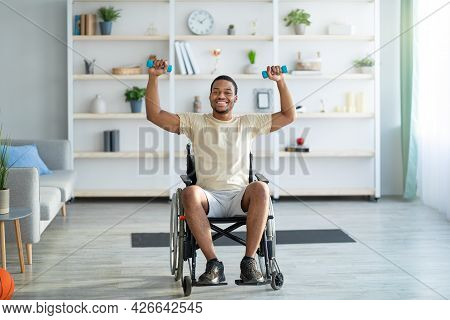 Rehab Exercises For Disabled People. Paraplegic Black Guy In Wheelchair Working Out With Dumbbells A