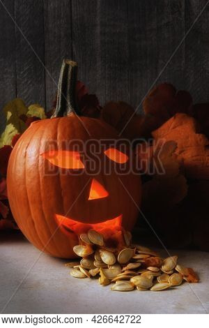 A Halloween jack o lantern with its seeds spilling out of its mouith. The pumpkin is carved and candle lit.