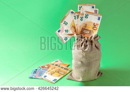 Bag With Euro Bills On A Green Background. Money Accumulation Concept. Stocks Of Money. Copy Space.