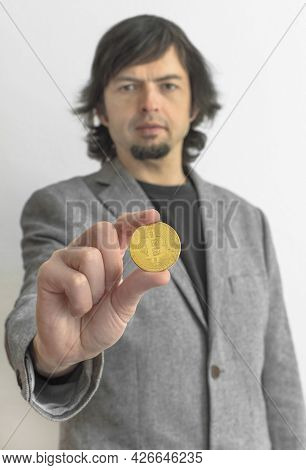 Businessman Wearing A Suit, Holding A Bitcoin Btc Crypto Currency Gold Coin, New Virtual Money Conce