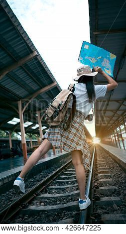 Young Female Tourists Are Happy To Travel. Traveler Woman With A Backpack, Camera, Map Walking On Ra