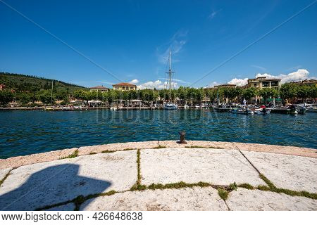 The Small Port Of Garda Town With Small Boats Moored, Tourist Resort On The Coast Of Lake Garda (lag