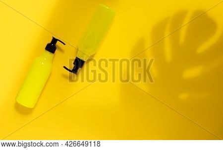 Mock-up Of Yellow Cosmetic Bottles With Shadow Leaves Of Monstera On A Yellow Background. A Creative
