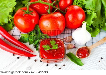 Ketchup, Ripe Tomatoes And Spices On The Table. The Concept Of Cooking Sauce Or Ketchup. Close-up.