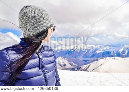 Caucasian Female Person Enjoy Winter Mountains Panorama In Sunny Ski Resort. Right Empty Blank Space