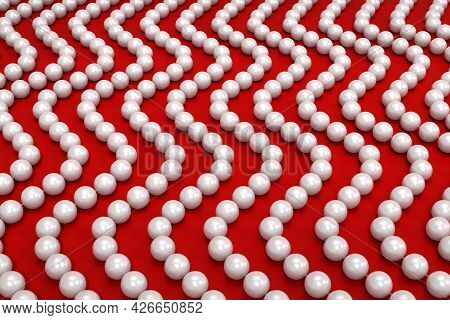 Background Of Threads With White Pearls On A Red Surface. The Beads Are Arranged In A Vertical Wave.