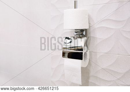 A Roll Of White Toilet Paper In A Modern Toilet. Washroom And Bathroom.
