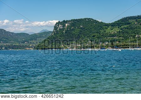 Large Group Of Sailing Boats Moored In Front Of The Small Village Of Bardolino, Coast Of Lake Garda