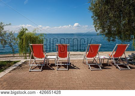 Four Empty Deck Chairs On A Beautiful Beach On Lake Garda (lago Di Garda) Between The Small Village