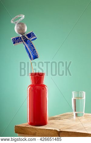 A Bright Red Vase On The Edge Of The Table And A Glass Half Filled With Water, Above The Vase Is An